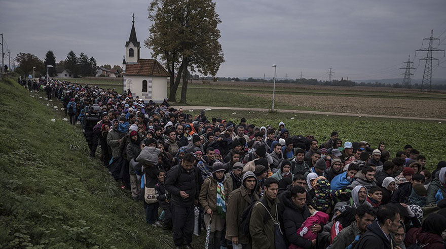 Migrants walking past a church, escorted by Slovenian riot police to a registration camp outside Dobova, Slovenia. The small Balkan nations along the path of the human migration through Europe have seen record numbers of refugees cross their borders, and have been overwhelmed in their ability to manage the human flow (Sergey Ponomarev, The New York Times - October 22, 2015).