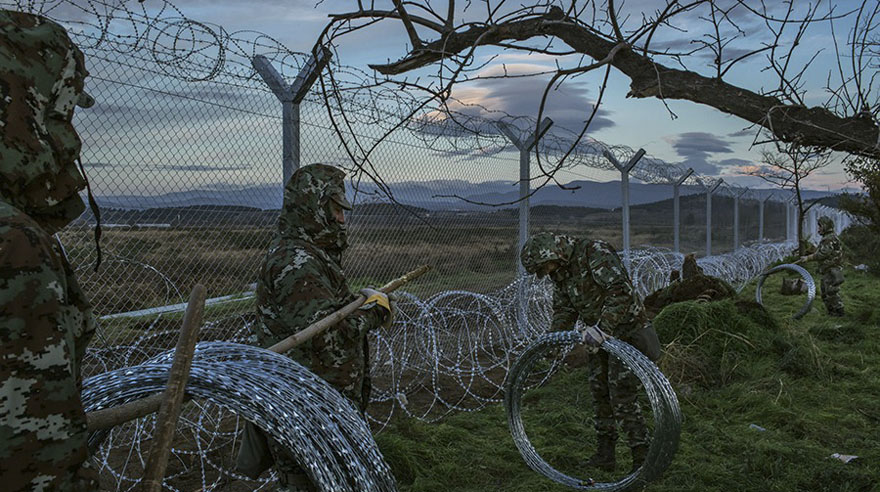 Macedonian soldiers on the Greek side of the border have built a border fence that divides their town of Gevgelija, in the background, from Idomeni, in Greece, where nearly 2,500 refugees were being barred from entering (Mauricio Lima, The New York Times - November 28, 2015).